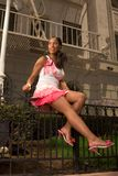 Black woman in pink skirt sitting on forged fence. Attractive young urban Afro-American woman in pink skirt with perfectly shaped legs sitting on wrought fence Stock Image