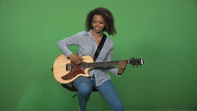 Black woman playing guitar. Young black female in shirt playing electric guitar on green background and sitting on chair stock video footage
