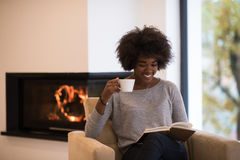Black woman reading book in front of fireplace royalty free stock photography