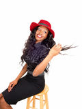 Black woman with red hat sitting on chair. Royalty Free Stock Images