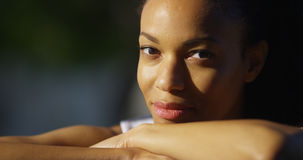 Black woman resting on arms looking at camera. Outdoors stock photos