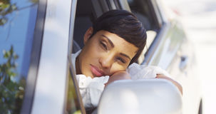 Black woman resting head out car window Stock Photos