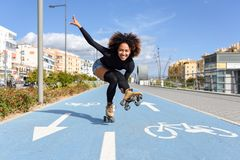 Black woman on roller skates riding on bike line. Young fit black woman on roller skates riding outdoors on bike line. Smiling girl with afro hairstyle Stock Photos