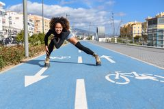 Black woman on roller skates riding outdoors on urban street. Young fit black woman on roller skates riding outdoors on bike line. Smiling girl with afro Stock Photography
