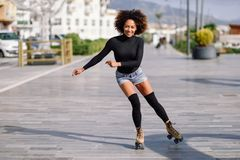 Black woman on roller skates riding outdoors on urban street. Young fit black woman on roller skates riding outdoors on urban street. Smiling girl with afro Royalty Free Stock Photo