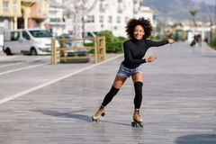 Black woman on roller skates riding outdoors on urban street. Young fit black woman on roller skates riding outdoors on urban street. Smiling girl with afro Royalty Free Stock Images