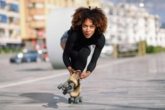 Black woman on roller skates riding outdoors on urban street. Young fit black woman on roller skates riding outdoors on urban street. Smiling girl with afro Stock Photography