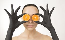 Black woman`s hands holding orange halves near her face. Black hands with bright tasty mandarin royalty free stock photography
