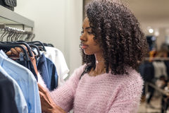 Black woman shopping clothes in a store royalty free stock photo
