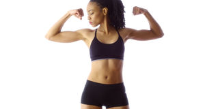 Black woman showing off muscles. Black woman flexing arms, showing off muscles Royalty Free Stock Image