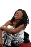 Black woman sitting on bed laughing Stock Photos