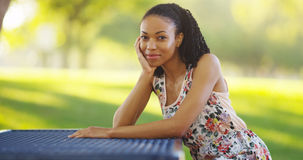 Black woman sitting on a park bench smiling Stock Photos