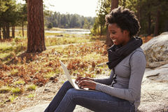Black woman sitting on a rock in countryside using computer Royalty Free Stock Images