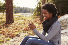 Black woman sitting on a rock in countryside using phone Royalty Free Stock Image