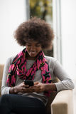Black woman sitting on sofa and using mobile phone. Young happy african american woman sitting on sofa and using mobile phone at luxury home Royalty Free Stock Photos
