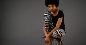 Black woman sitting on stool Stock Photo