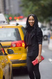 Black Woman Smiling. Smiling African-American woman on city street, amidst taxi cabs, with blurred background Stock Images