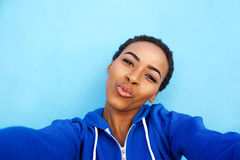 Black woman smiling against blue wall with hands behind head Stock Photo