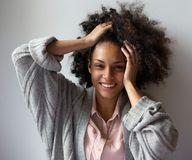 Black woman smiling with hands in hair Royalty Free Stock Photos