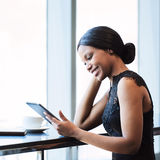 Black woman smiling while holding and looking at a tablet. Fashionable and attractive young african woman wearing black busy looking at a digital tablet that she Royalty Free Stock Images