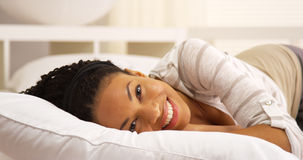 Black woman smiling and laughing on bed looking at camera Royalty Free Stock Photos