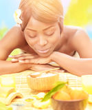 Black woman on spa resort. Attractive black woman relaxed on luxury spa resort, lying down on massage table with closed eyes on the beach in sunny day stock photos