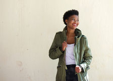 Black woman standing outside with green jacket. Portrait of a smiling black woman standing outside with green jacket Stock Image