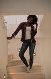 Black woman standing on the stairs. Portrait of a beautiful young African American women standing on the stairs in her luxurious home Royalty Free Stock Photos