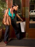 Black woman stuck in door (focus on bag). African-American woman wearing jeans getting in apartment building after shopping with her bags stuck in door (focus on Royalty Free Stock Images