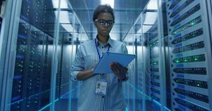 Black woman with tablet checking server hardware. Adult African American woman using tablet while walking among server racks in data center corridor and doing royalty free stock photo