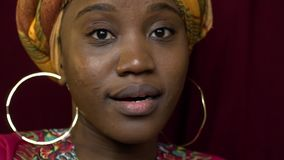Black woman in traditional headgear is surprised, slow motion stock video footage