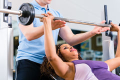 Black woman with Trainer lifting weights in gym for fitness Royalty Free Stock Photo