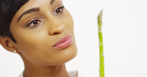 Black woman trying asparagus and smiling Royalty Free Stock Photography
