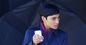 Black woman with umbrella standing in rain using mobile phone Stock Photography