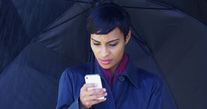 Black woman with umbrella standing in rain using mobile phone Stock Photos
