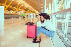 Black Woman upset and frustrated at the airport with flight canc Stock Photo