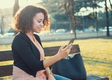Black woman using app on mobile phone Stock Photo