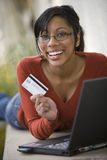 Black Woman Using Credit Card And Laptop Outside Stock Photo