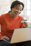 Black woman using credit card and laptop. Smiling African American woman shopping online with credit card and laptop computer Royalty Free Stock Photography