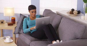 Black woman using laptop on couch Royalty Free Stock Photos