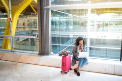 Black woman using mobile phone and laptop at the airport sitting Stock Photography