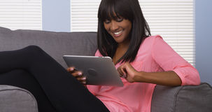 Black woman using pad in pink shirt Royalty Free Stock Photography