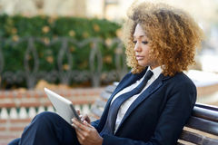 Black woman using tablet computer in town Stock Photos