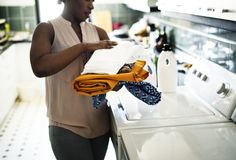 Black woman using washing machine doing the laundry Stock Photography
