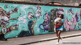 Black woman walking holding her son, in front of  on a wall decorated in graffiti Royalty Free Stock Photography