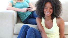 Black woman watching TV while a friend is on a couch stock footage