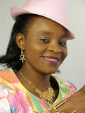 Black woman wearing a pink hat. Is smiling at the camera royalty free stock images