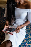 Black woman in white dress. she is taking a device in her hands chatting in internet. Blue carpet in luxury vip hotel Stock Photo