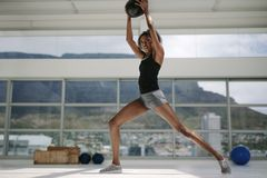 Woman working out with fitness ball. Black woman working out with fitness ball. African woman stretching indoors with medicine ball at gym royalty free stock photos
