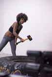 Black woman workout with hammer and tractor tire Stock Photography